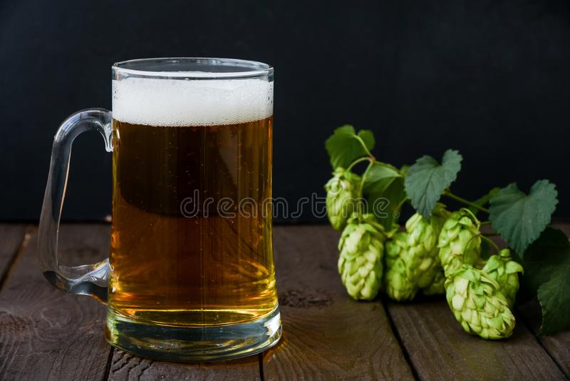 Octoberfest foamy beer in the mug. On the wooden table royalty free stock image