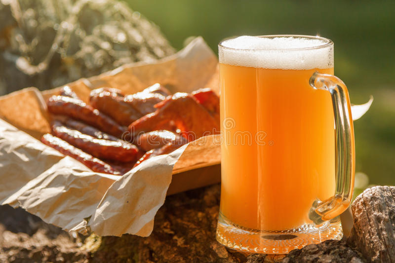 Octoberfest mug beer with food picnic. Octoberfest mug beer with food on natural background royalty free stock images
