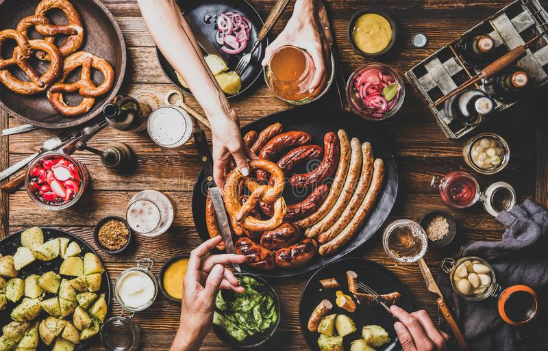 Octoberfest party dinner table with beer, snacks and peoples hands. Flat-lay of Octoberfest party dinner table with grilled meat sausages, pretzel pastry royalty free stock photos
