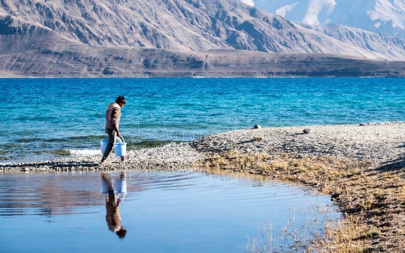 5 octobre 2017 : Un homme écopant l'eau dans le lac Pangong avec le Mountain View, Inde de Ladakh photographie stock libre de droits