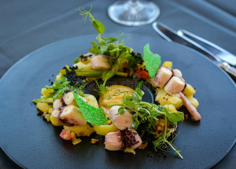 Octopus dish on black plate in restaurant. stock image