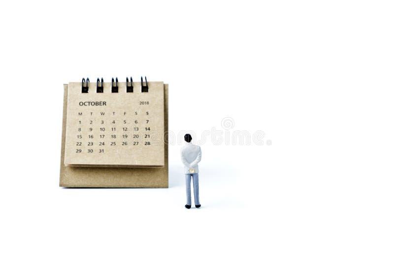 octubre Haga calendarios la hoja y al hombre plástico miniatura en el backg blanco fotografía de archivo