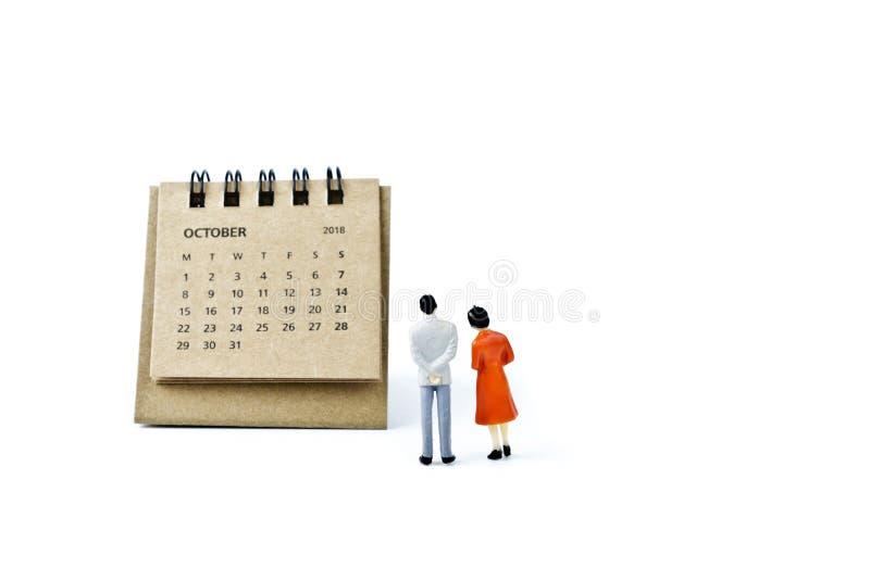 octubre Haga calendarios la hoja y hombre y mujer plásticos miniatura en w foto de archivo libre de regalías