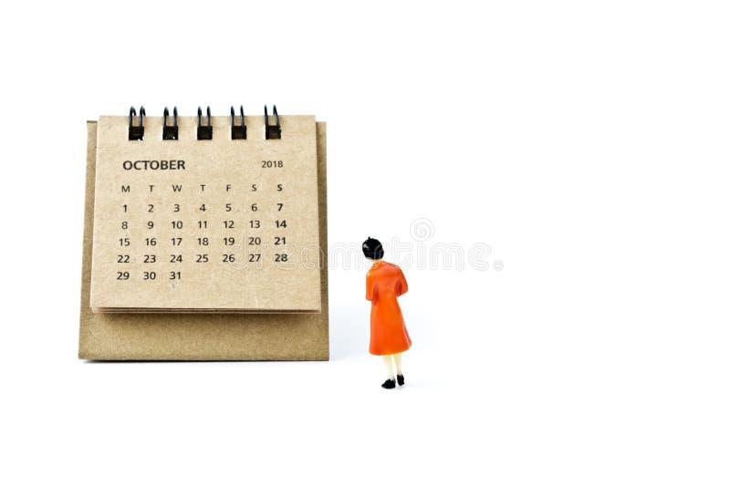 octubre Haga calendarios la hoja y a la mujer plástica miniatura en el CCB blanco imagen de archivo