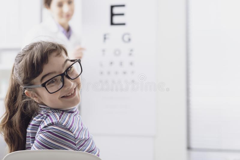 Oculist testing a young patient`s eyesight using an eye chart. Ophthalmology and eyesight concept royalty free stock images