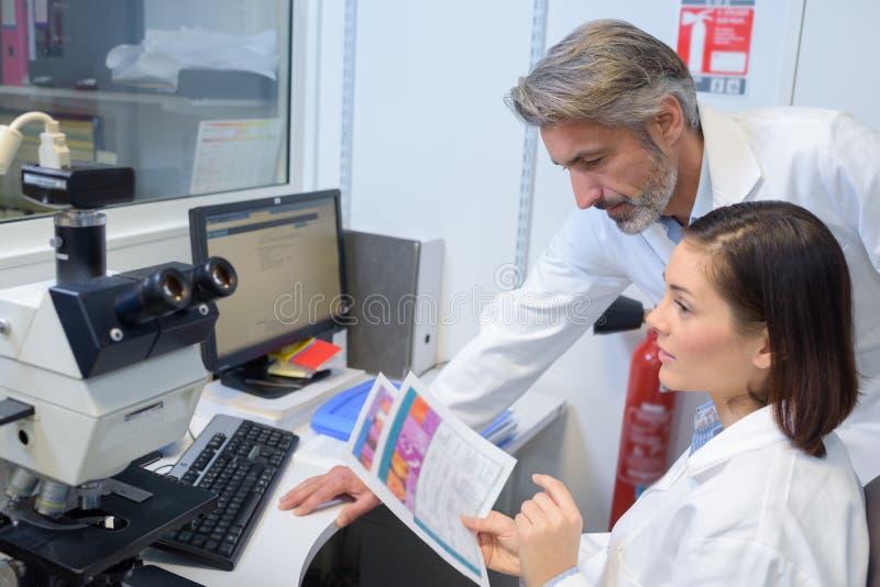 Oculista de sexo femenino y de sexo masculino que se sienta con el dispositivo oftalmológico fotografía de archivo libre de regalías