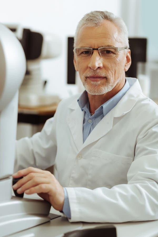 Oculista experimentado profesional que se sienta en la tabla imagenes de archivo
