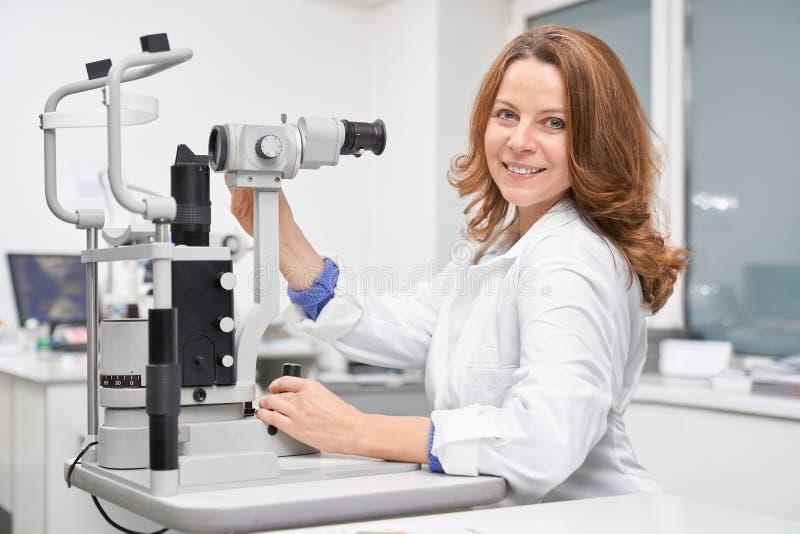 Oculista femminile che lavora nella clinica e che controlla vista fotografie stock
