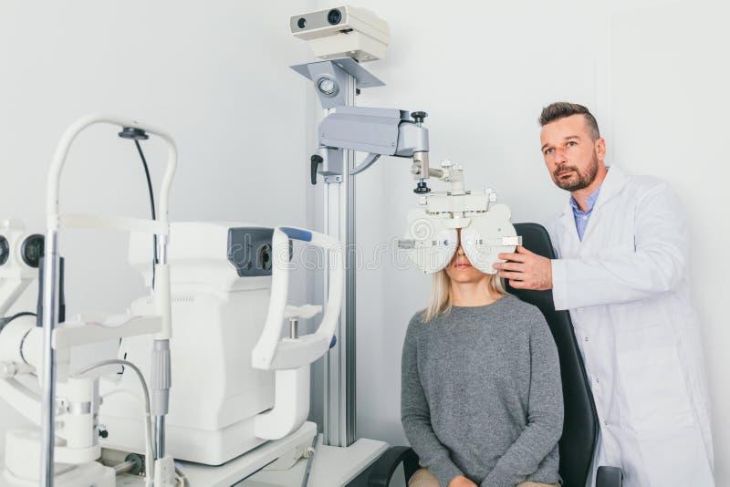 Oculista que comprueba los ojos del paciente en una máquina fotografía de archivo