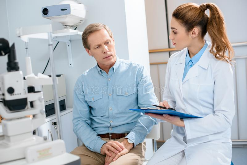 oculista que escreve o diagnóstico após o exame do meio fotografia de stock