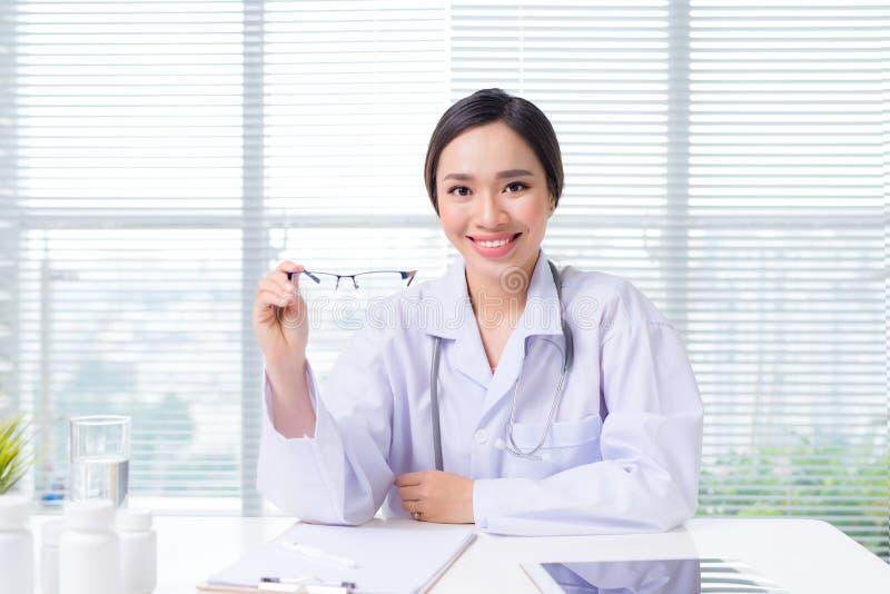 Oculiste féminin donnant une paire de lunettes image libre de droits