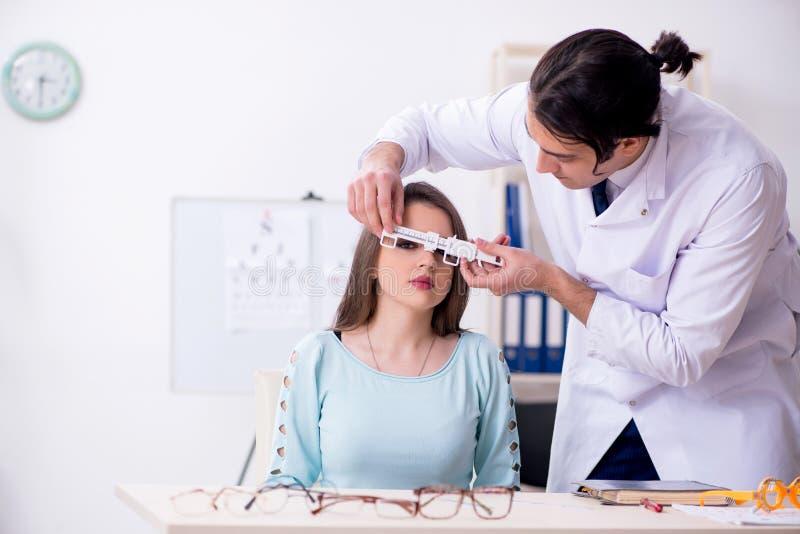Oculiste masculin de visite de docteur de jeune femme photo stock