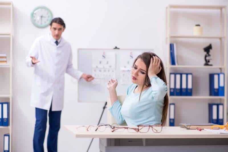 Oculiste masculin de visite de docteur de jeune femme photographie stock