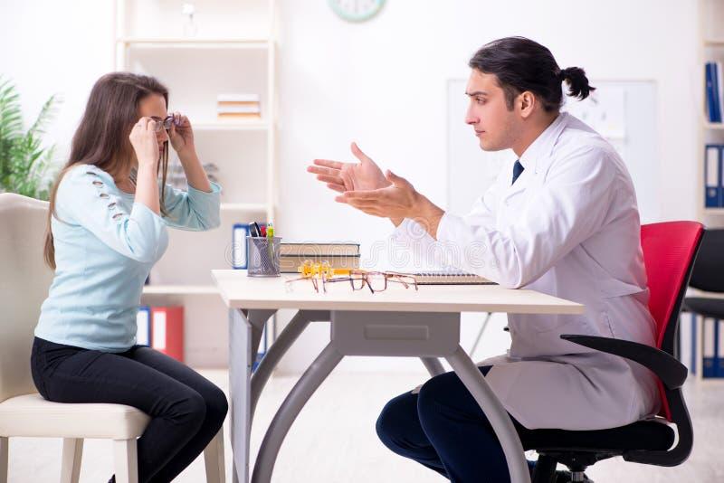 Oculiste masculin de visite de docteur de jeune femme photos stock