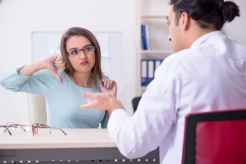 Oculiste masculin de visite de docteur de jeune femme images libres de droits