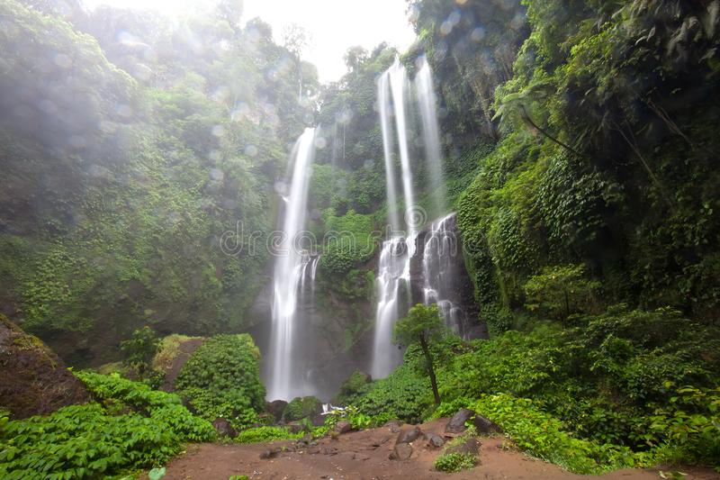 Ocultado en la cascada hermosa de Sekumpul de las selvas en Bali, Indonesi fotografía de archivo