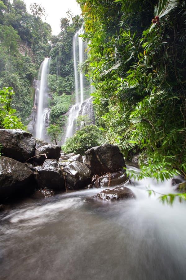 Ocultado en la cascada hermosa de Sekumpul de las selvas en Bali, Indonesi foto de archivo