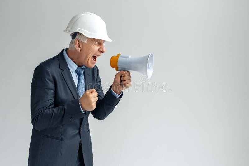 Ocupação profissional Construtor na posição do capacete de segurança isolado na gritaria cinzenta no punho de fatura irritado do  imagem de stock royalty free