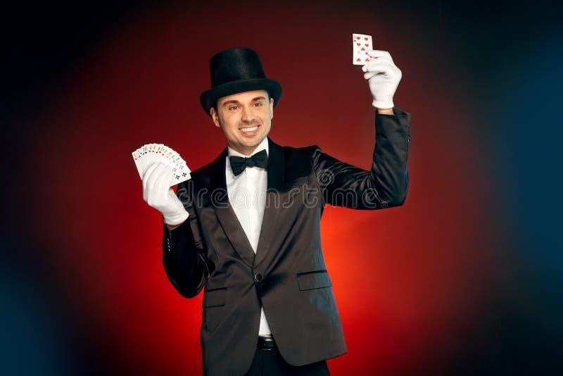 Ocupação profissional O mágico na posição das luvas e do chapéu do terno isolado na parede que faz truques com cartões mostra o s foto de stock royalty free