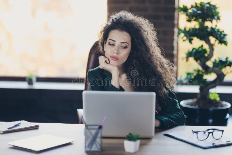 A ocupação representativa do mediador imobiliário sério ascendente próximo da foto senta o PC do dispositivo do usuário do uso da fotos de stock