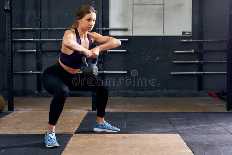 Ocupación de la mujer joven con Kettlebell en gimnasio imagen de archivo libre de regalías
