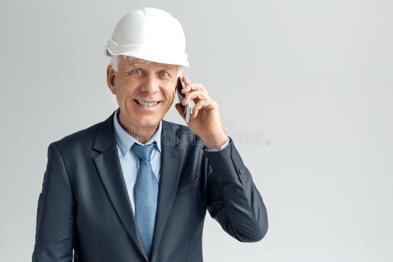 Ocupación profesional Constructor en la situación del casco aislado en hablar gris en la sonrisa del smartphone emocionada fotos de archivo