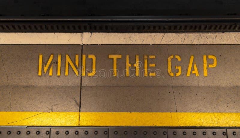 Ocupe-se da diferença que o sinal típico pintou em uma borda da plataforma do tubo Aviso pintado no assoalho Ocupe-se da diferenç fotos de stock royalty free