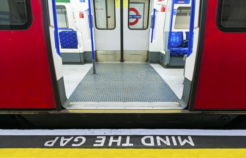 Ocupe-se do sinal da diferença com o trem de pressa em Londres no subsolo imagens de stock