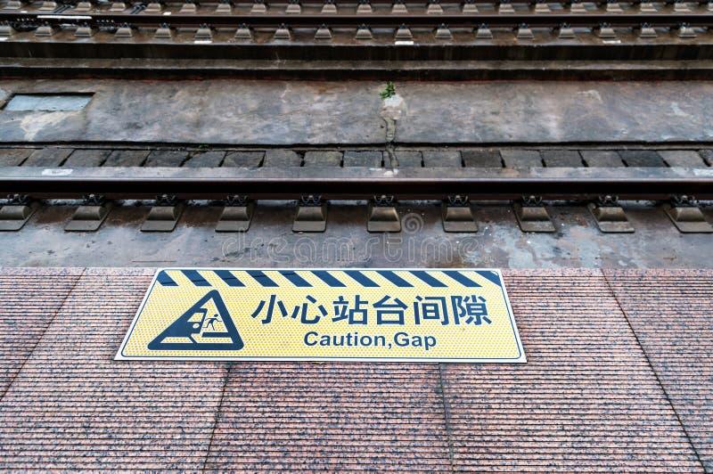Ocupe-se do sinal da diferença pintado na borda da plataforma do ` s do estação de caminhos-de-ferro fotografia de stock royalty free