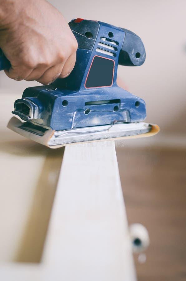 Oczodołowy sander w użyciu, sanding stary drzwi dla nowego liźnięcia farba zdjęcia royalty free