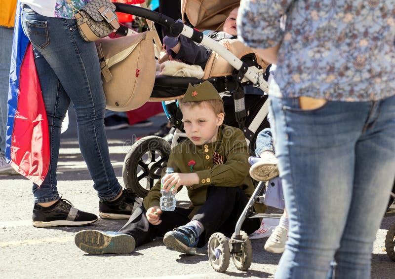 Odödligt regemente på Moskvagatan Tusentals marscherar för att minnas släktingar för världskrig 2 Ett pojkesammanträde på golvet  royaltyfri foto