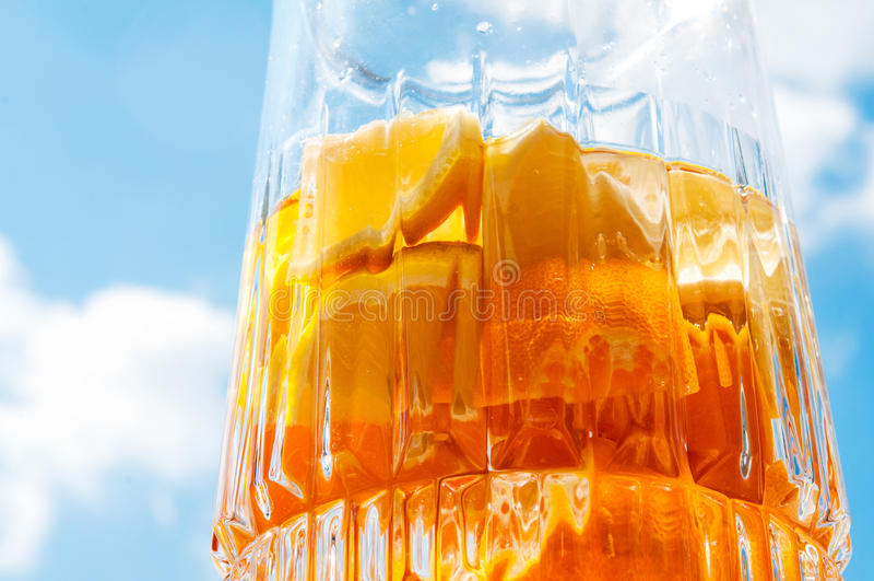 Odświeżać do domu robić pomarańczowy cytryny sangria w szklanym dzbanku nad niebieskiego nieba tłem, tangerine lub lemoniada i zdjęcie stock