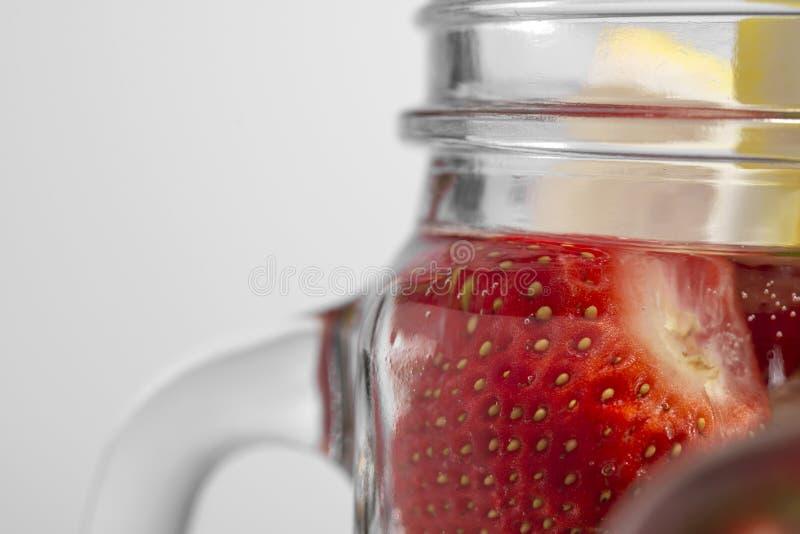Odświeżająca owoc woda od truskawek i cytryny w szklanym kubku w górę białego tła dalej obrazy royalty free