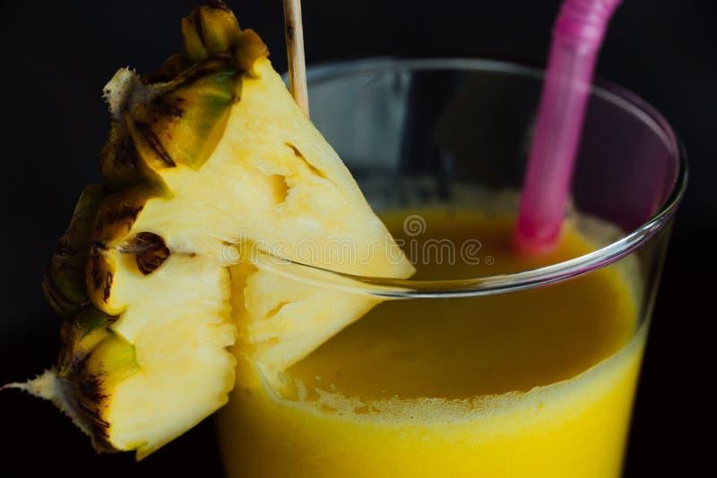 Odświeżający ananasowy koktajlu szkło z plasterkami ananas, różowe sok słoma i dekoracja, zdjęcia royalty free