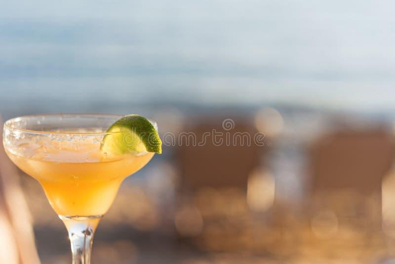 Odświeżający Klasyczny Margarita koktajl Z wapnem I solą plażą Przy zmierzchem Na Zamazanym tle zdjęcia stock