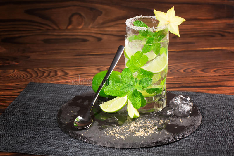 Odświeżający koktajl z rumem, wapno, mennica, miażdżył lód i carambola na drewnianym tle Szkło pełno mojito kosmos kopii obraz royalty free