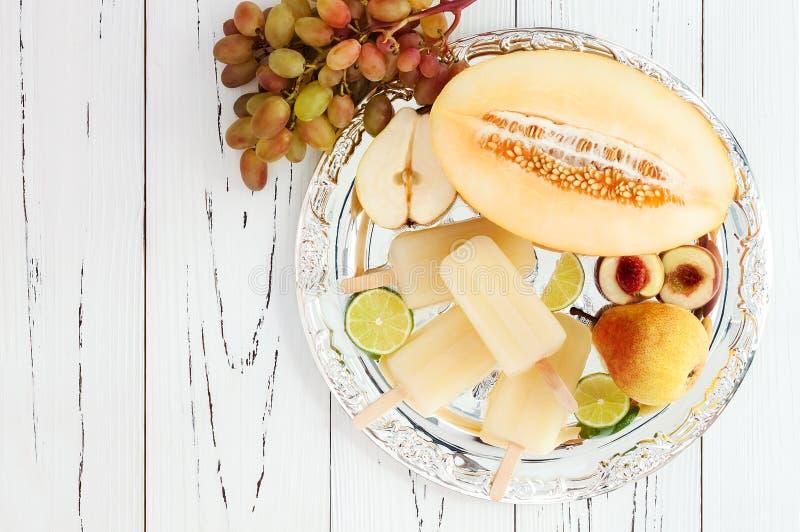 Odświeżający lód strzela nad srebną tacą Bonkreta, brzoskwinia, winogrono, wapno, miodunki sangria biali paletas - popsicles Odgó obrazy royalty free
