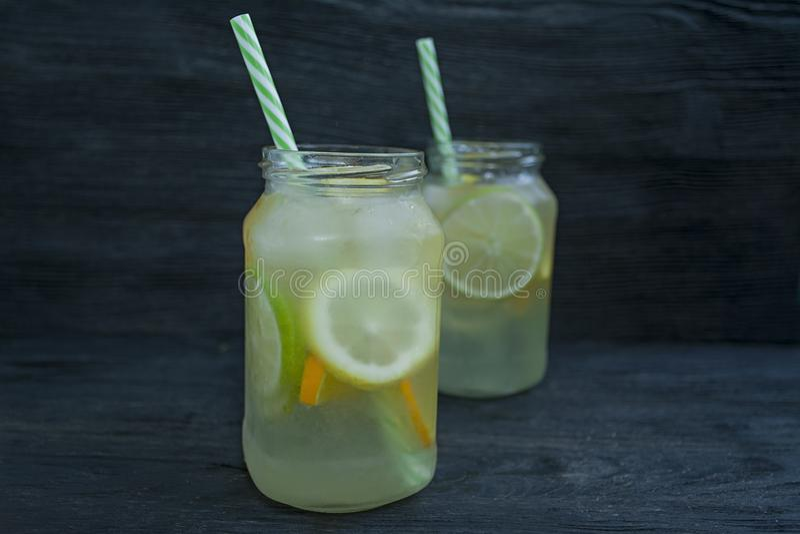 Odświeżający lato napój od cytrus owoc Napój od wapna, cytryna, pomarańcze drewniany t?o zmrok zdjęcia royalty free