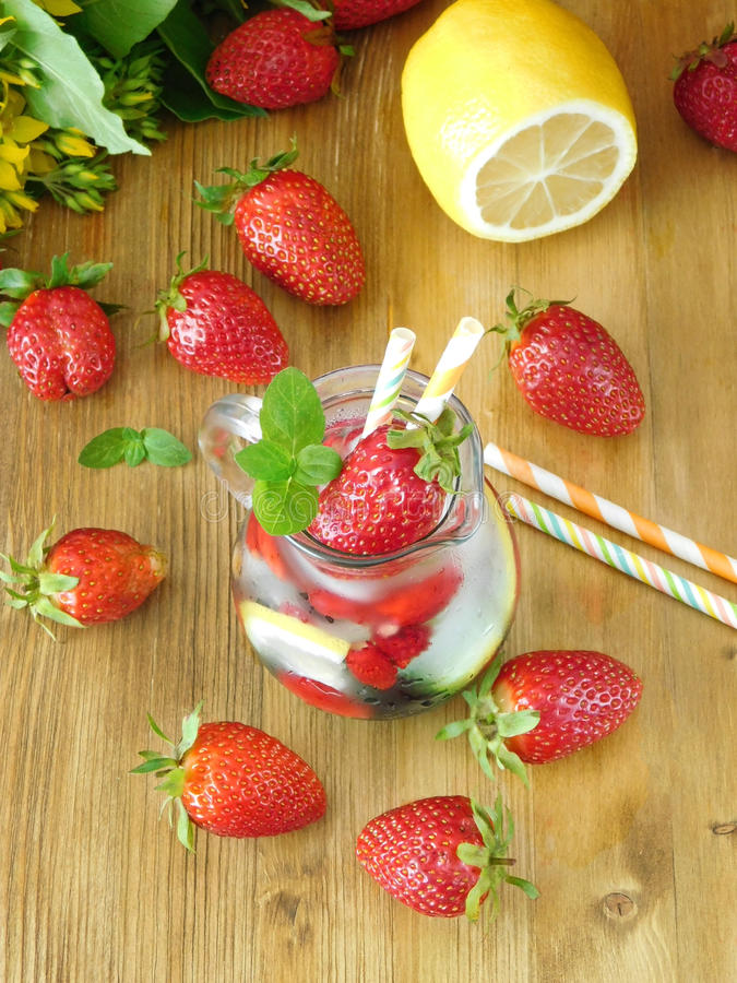 Odświeżający napój z kostkami lodu, truskawkami i mennicą, zdjęcie royalty free