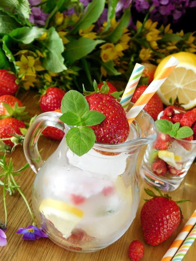 Odświeżający napój z kostkami lodu, truskawkami i mennicą, fotografia stock