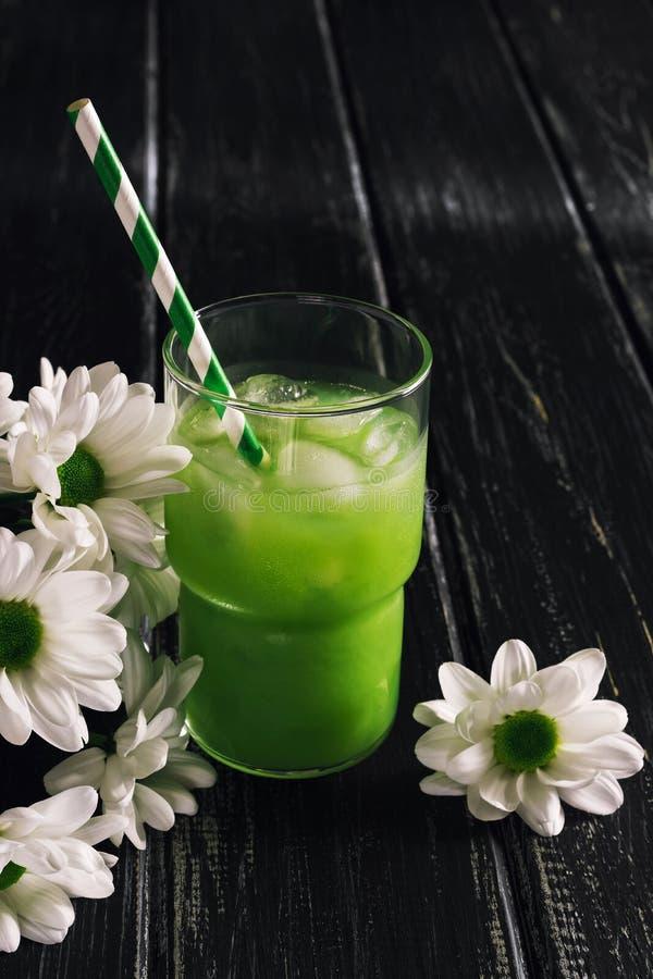 Odświeżający zielony napój z lodem, pasiastą słomą i białymi kwiatami, Zielony sok na drewnianym drewnianym stole Lata zimna kokt zdjęcie stock