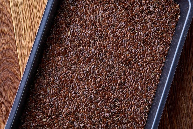 Odżywczy flaxseed na wypiekowej tacy nad drewnianym tłem, selekcyjna ostrość, płytka głębia pole obrazy stock