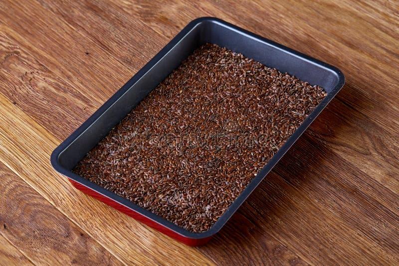 Odżywczy flaxseed na wypiekowej tacy nad drewnianym tłem, selekcyjna ostrość, płytka głębia pole zdjęcie stock
