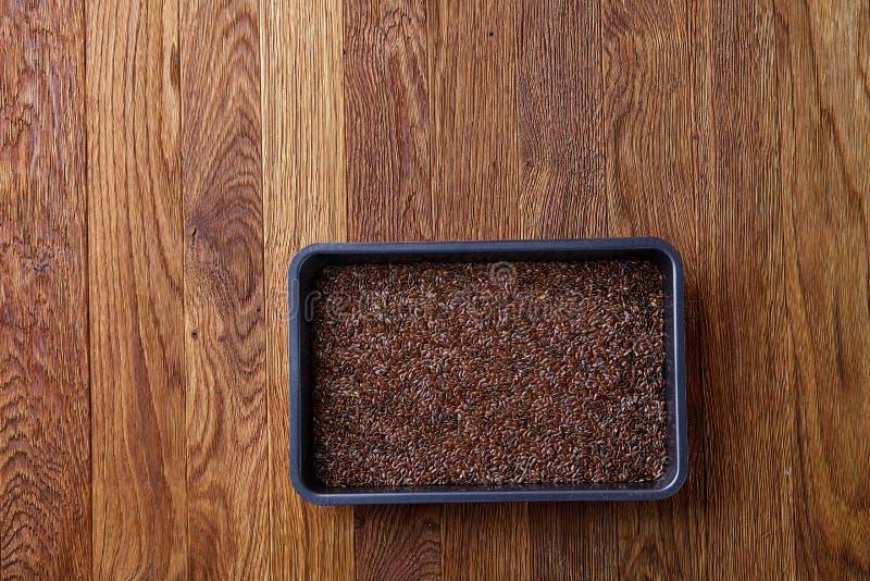 Odżywczy flaxseed na wypiekowej tacy nad drewnianym tłem, selekcyjna ostrość, płytka głębia pole zdjęcie royalty free