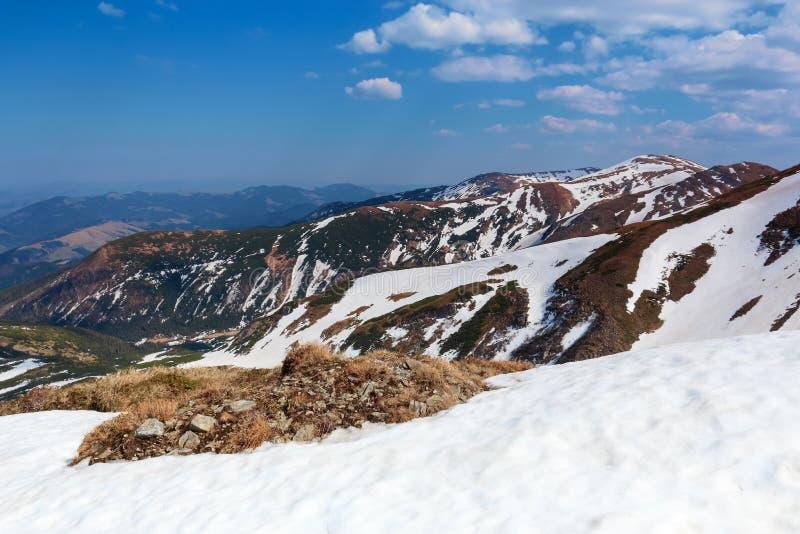Od śniegu zakrywający gazon otwiera widok wysokie góry z śniegi zakrywającymi wierzchołkami, niebieskie niebo Wspaniały wiosna kr obraz stock