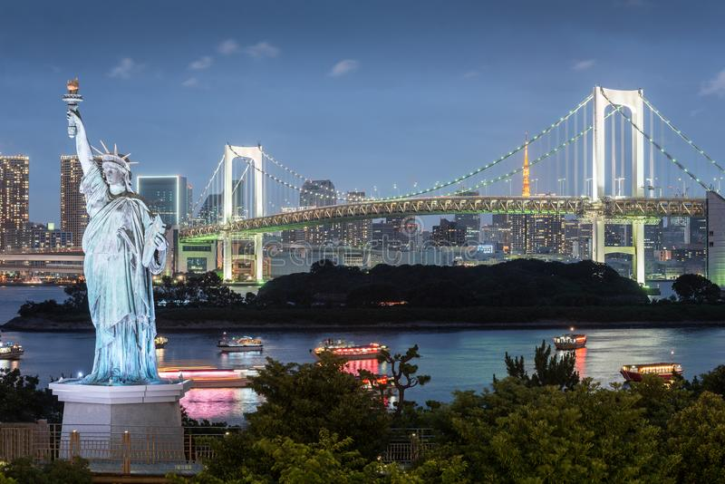 Odaiba Statue of Liberty with rainbow bridge and Tokyo tower in evening. Landmarks of Tokyo, Japan royalty free stock photos
