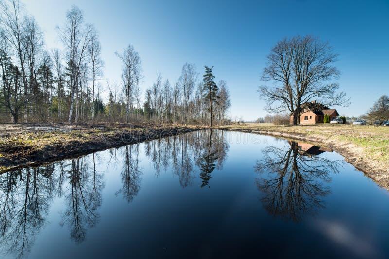 Odbicia dom na wsi w stawie obraz stock