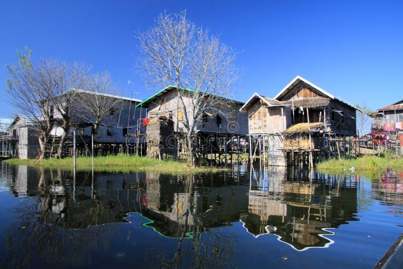 Odbicia tradycyjnych stilts drewniani domy w gładkim jako szkło wody kontrastowanie z bezchmurnym niebieskim niebem - Inle jezior zdjęcia stock