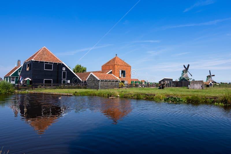 Odbicia w wodzie wiatraczki na uroczym dniu z niebieskim niebem i gospodarstwa rolne, ZAANSE SCHANS holland obrazy royalty free