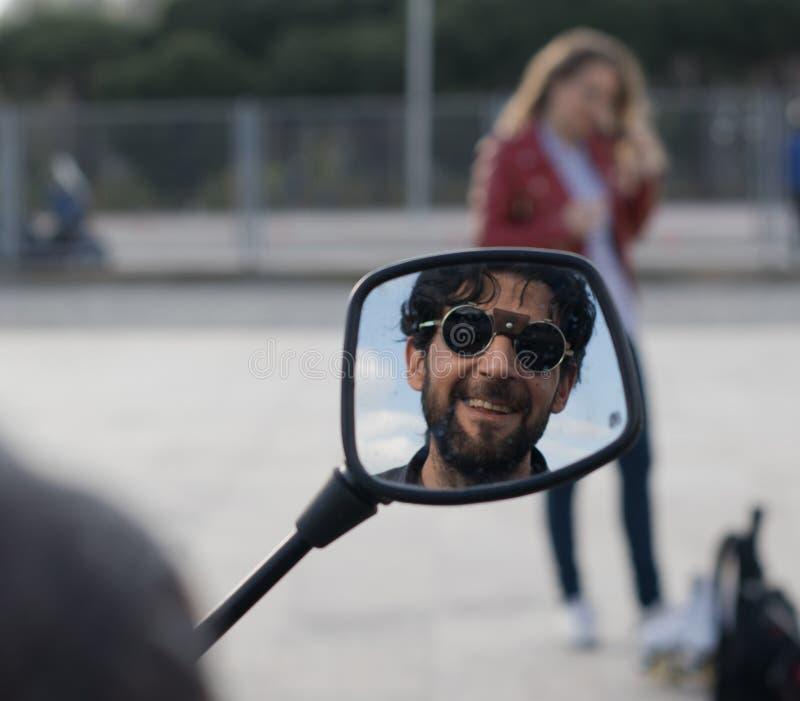Odbicie mężczyzna ono uśmiecha się w motocyklu lustrze z szkłami i broda obraz stock